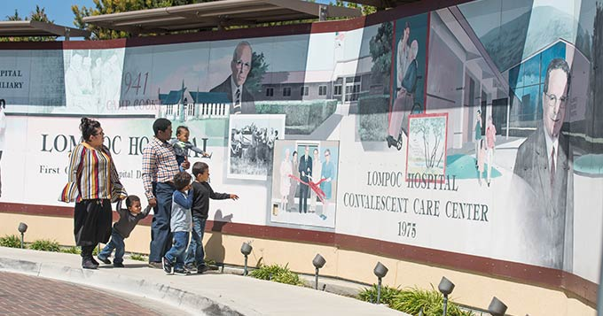 local family looking at faded  Hospital Mural